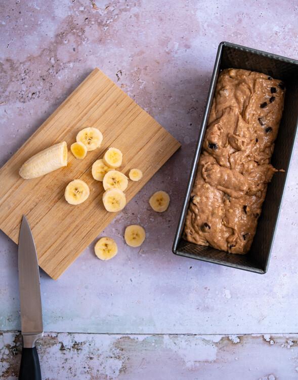 Der Teig für das vegane Bananenbrot wird in eine Kastenform gegeben. Neben der gefüllten Kastenform liegt ein kleines Holzbrett auf dem einige Bananenscheiben liegen.