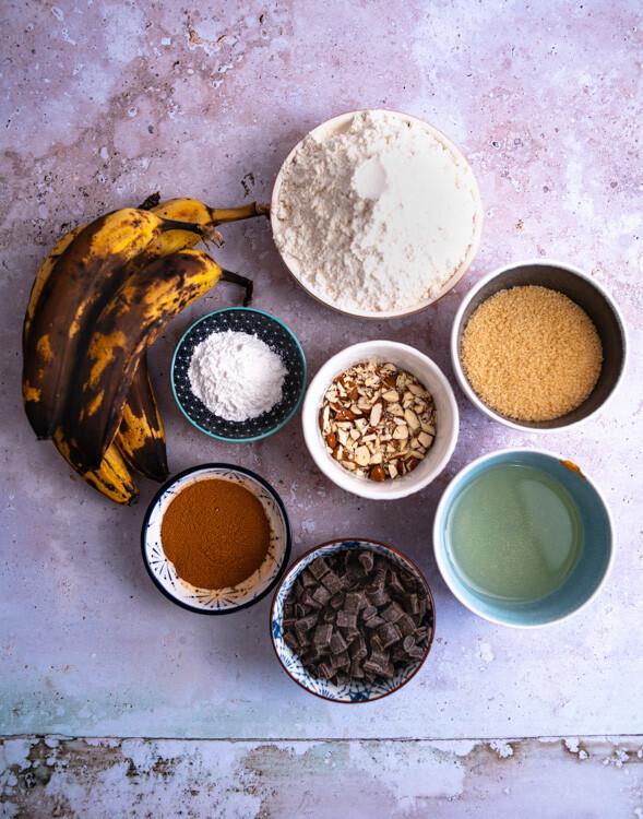Die Zutaten für das vegane Bananenbrot sind reife Bananen, Weizenmehl, brauner Zucker, Backpulver, Walnüsse, Öl, Zimt und Schokochips.