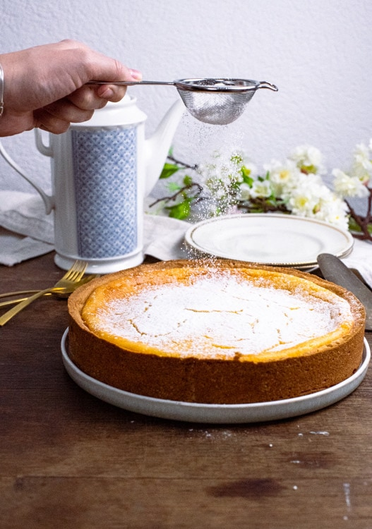 Nach dem Backen wird das Käsekuchen Rezept mit etwas Puderzucker vollendet.