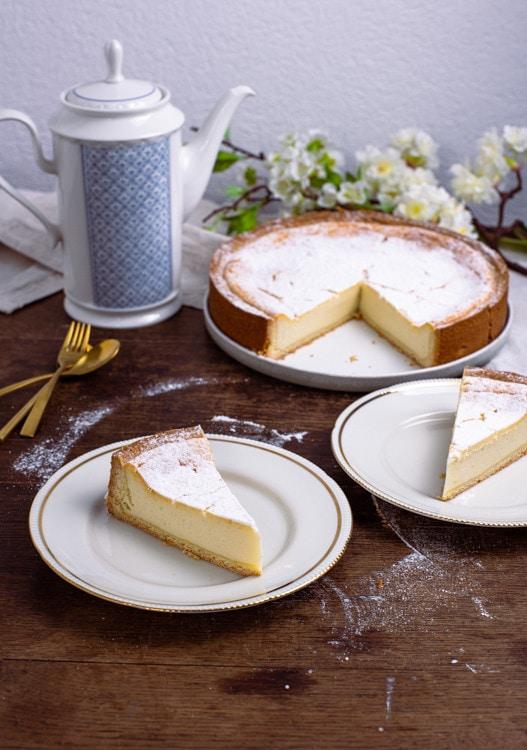Käsekuchen Rezept mit Quark nach Omas Rezept steht angeschnitten auf dem Tisch. Zwei Stücke des Käsekuchens stehen im Vordergrund des Fotos, der restliche, angeschnittene Käsekuchen steht im Hintergrund.