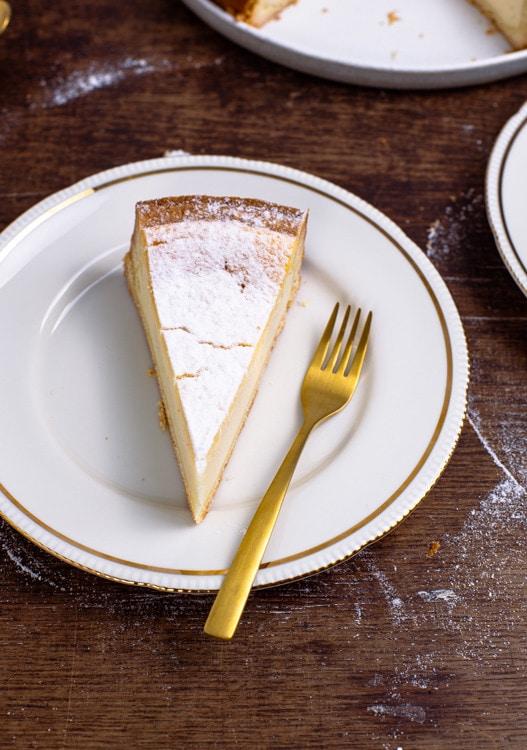 Ein Stück Käsekuchen liegt auf einem weißen Teller mit Goldrand. Eine goldene Gabel liegt neben dem Kuchenstück auf dem Teller.