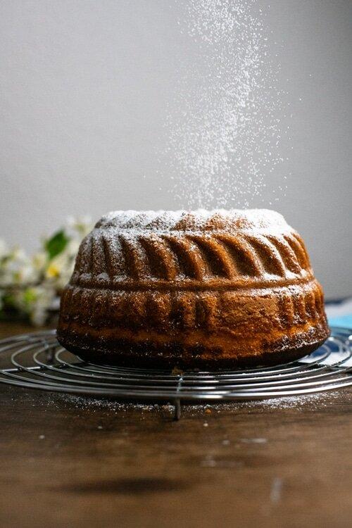 Der fertige gebackene Marmorkuchen in Guglhupfform steht auf einem Kuchengitter und wird mit Puderzucker bestreut.
