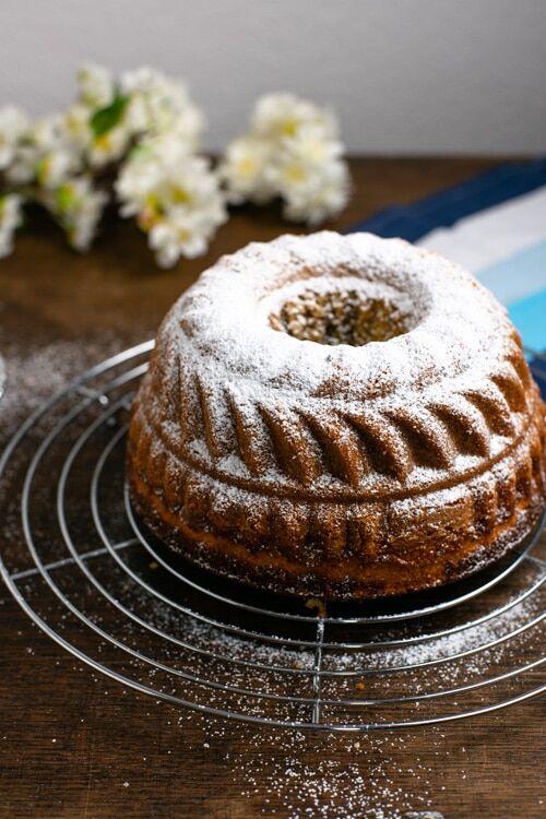 Der Marmorkuchen steht auf einem Kuchengitter und ist mit Puderzucker bestreut.