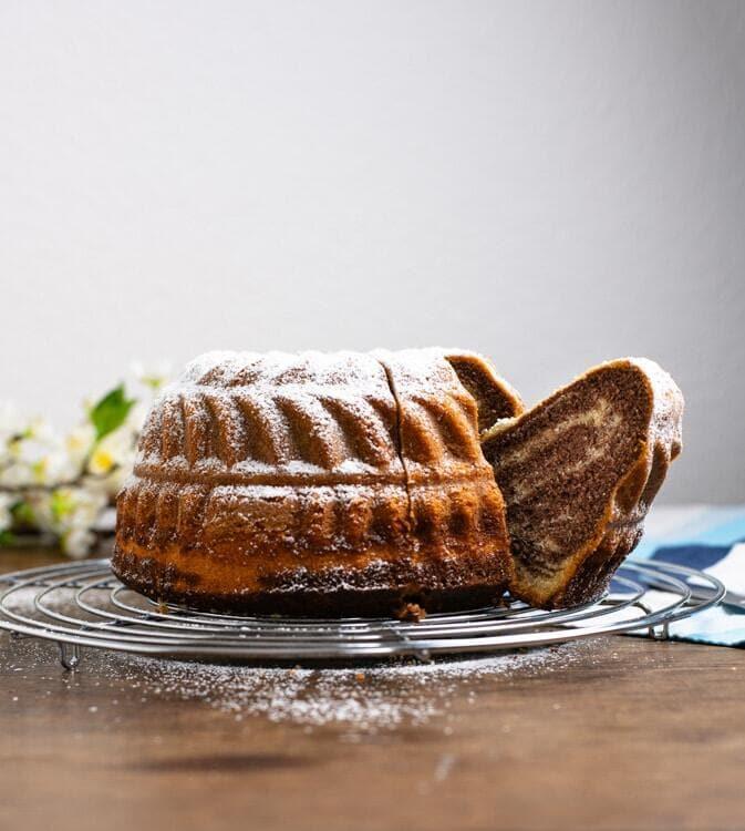 Marmorkuchen steht auf einem Kuchengitter. Der Kuchen ist in einer Guglhupfform gebacken. Ein Stück ist heraus geschnitten und lehnt etwas nach außen.