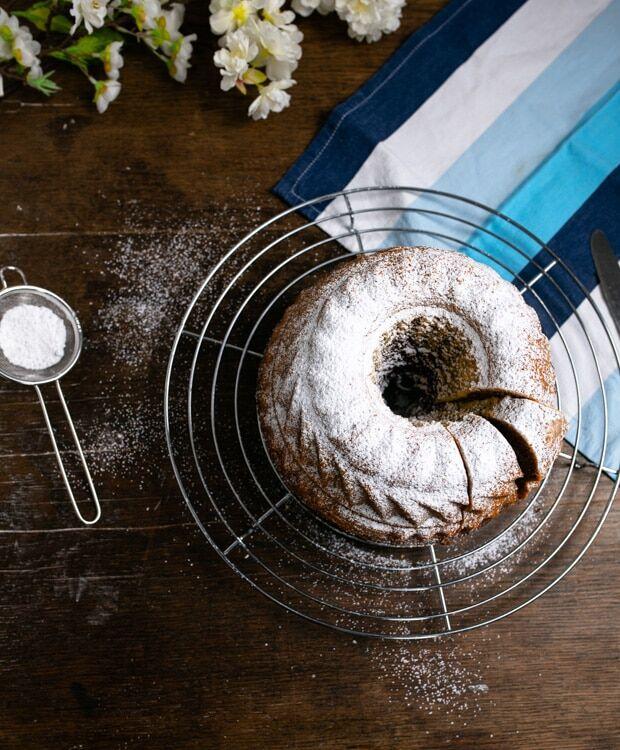 Marmorkuchen, gebacken in einer Guglhupfform steht auf einem Kuchengitter. Der Kuchen ist mit Puderzucke bestreut und es sind zwei Stücke vom Kuchen abgeschnitten.