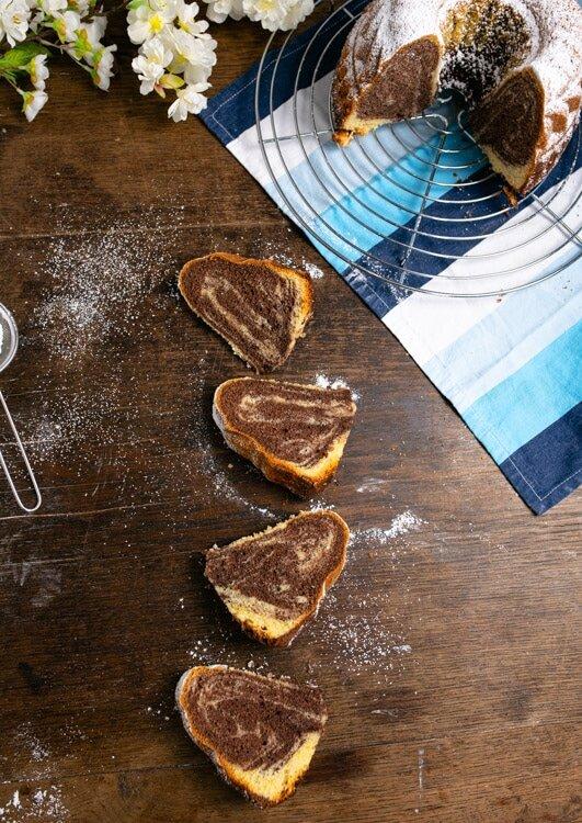 Vier Stücke Marmorkuchen liegen auf einem Holztisch. Das Marmormuster ist gut zu erkennen. Der restliche Marmorkuchen steht auf einem Kuchengitter.