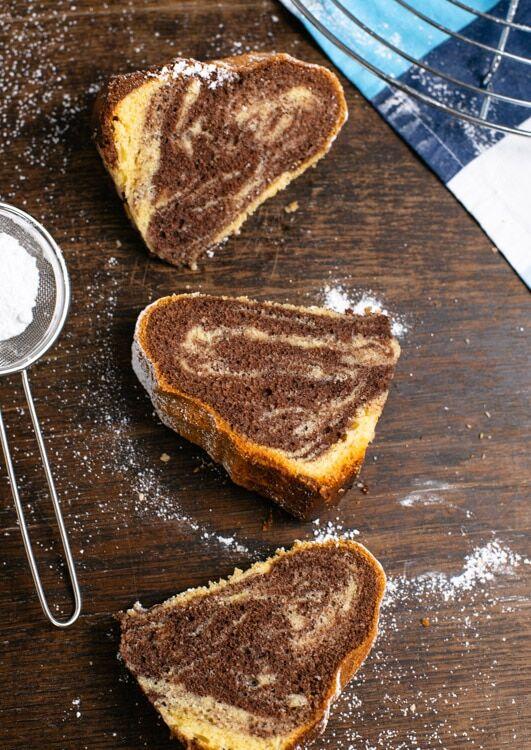 Drei Stücke Marmorkuchen liegen auf dem Tisch. Dar Marmormuster ist gut zu erkennen.