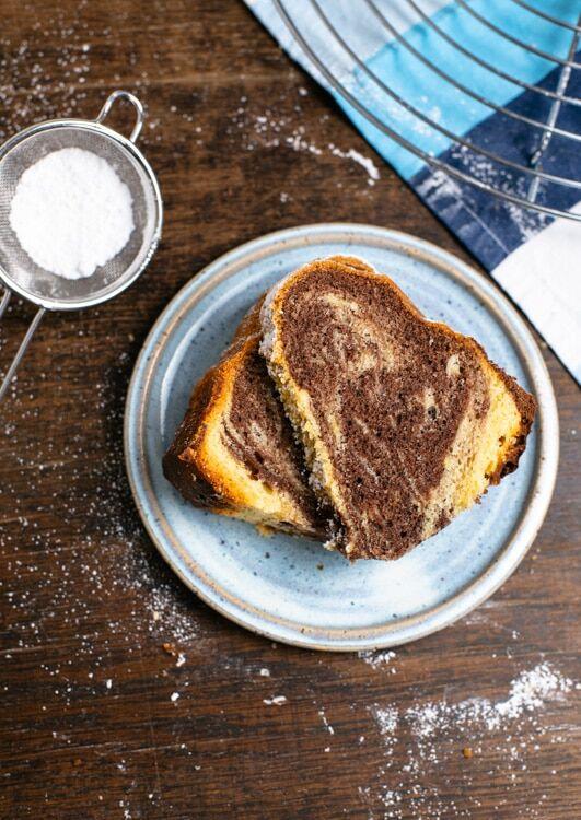 Zwei Stücke Marmorkuchen liegen auf einem hellblauen, handgetöpferten Teller. Das Marmormusterals hellem und dunklem Teig ist gut zu erkennen. Neben dem Teller liegt ein Sieb mit Puderzucker. Der restliche Kuchen steht auf einem Kuchengitter.
