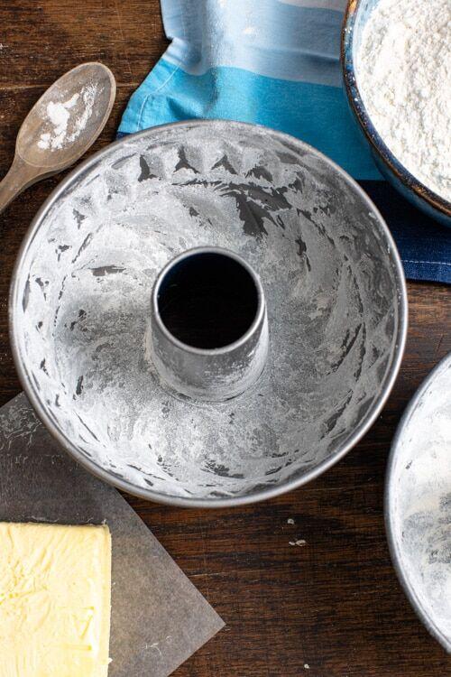 Die Guglhupfform, in der der Marmorkuchen gebacken wird, muss vor dem Backen zunächst mit Butter eingepinselt und mit Mehl bestäubt werden.