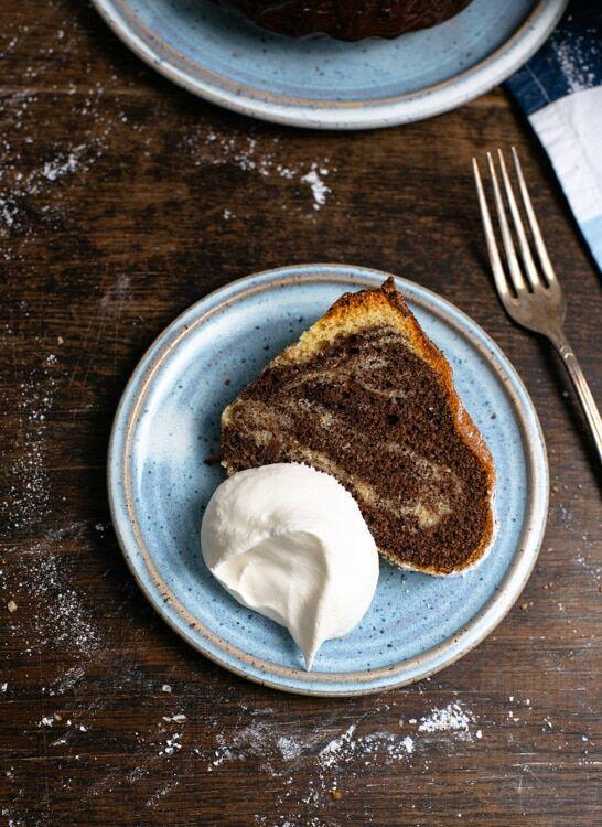Ein Stück Marmorkuchen liegt auf einem hellblauen, handgetöpferten Teller. Das Marmormuster ist gut zu erkennen. Eine kleine Portione Schlagsahne befindet sich auf dem Teller.