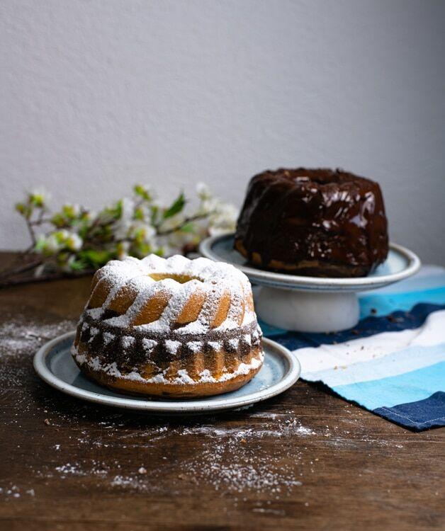 Auf dem Foto sind zwei kleine Guglhupfe zu sehen. Einer der Marmorkuchen ist mit Puderzucker streut. Dieser steht im Vordergrund des Fotos. Der andere Marmorkuchen ist mit Schokolade glasiert und steht etwas weiter im Hintergrund.