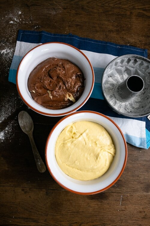 Die Hälfte des Teiges wird mit Kakao und etwas Milch versehen. Auf dem Bild ist der helle und der dunkle Teig zu sehen, sowie die vorbereitete Guglhupfform.