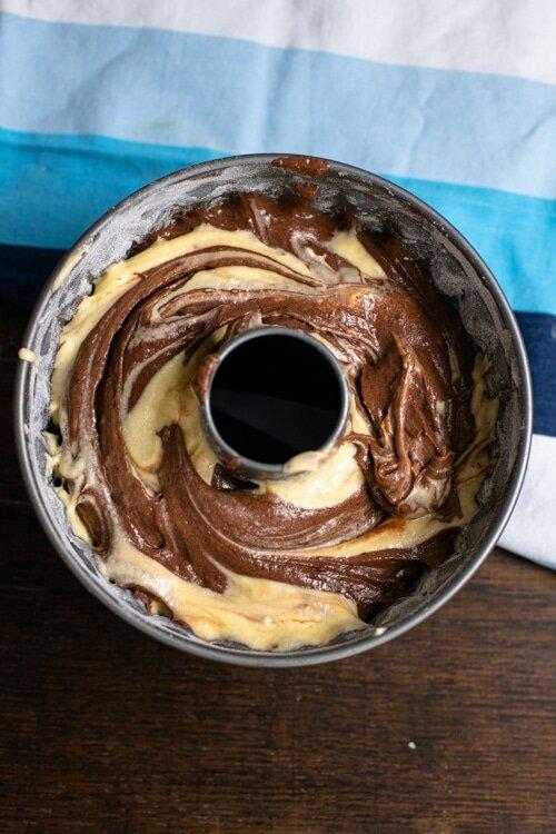 Der ungebackene Marmorkuchen ist in der Form, der Teig bereits marmoriert. Das Marmormuster ist gut zu erkennen.