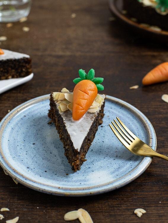Ein stück Rüblikuchen mit einer Marizpankarotte liegt aufeinem Reller. Die Textur des Kuchens ist sehr gut zu erkennen.