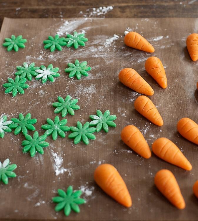 Aus dem Orangenen Marizpan wurden Karotten geformt. Das grüne Marizpan wurde ausgerollt und daraus kleine Blüten ausgestochen.