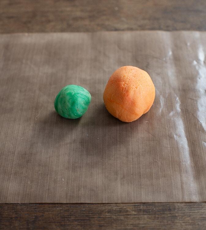 Auf einem Stück Backpapier liegen oranges und grünes Marizpan.