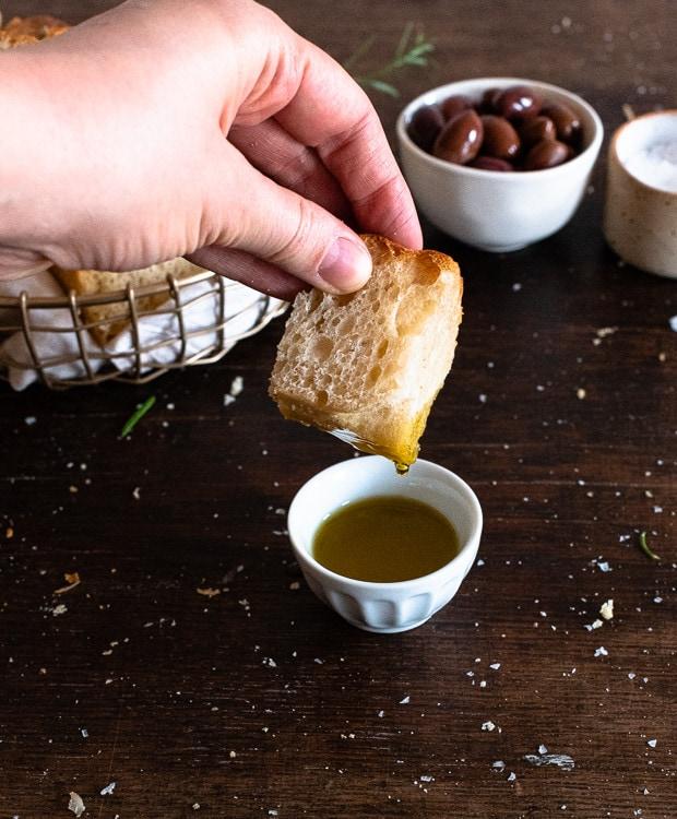 Ein stück italienisches Focaccia Brot wird in Olivenöl getaucht.