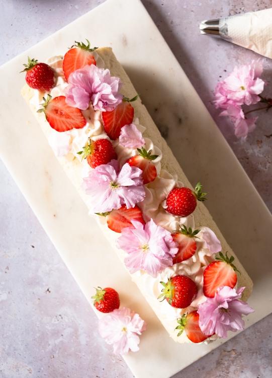 Fertig dekorierte Biskuitrolle mit Schlagsahne, frischen Erdbeeren und essbaren Blüten.