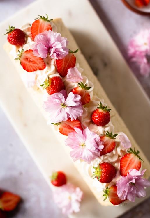 Die Biskuitrolle ist dekoriert mit geschlagener Sahne, frischen Erdbeeren und essbaren Blüten.