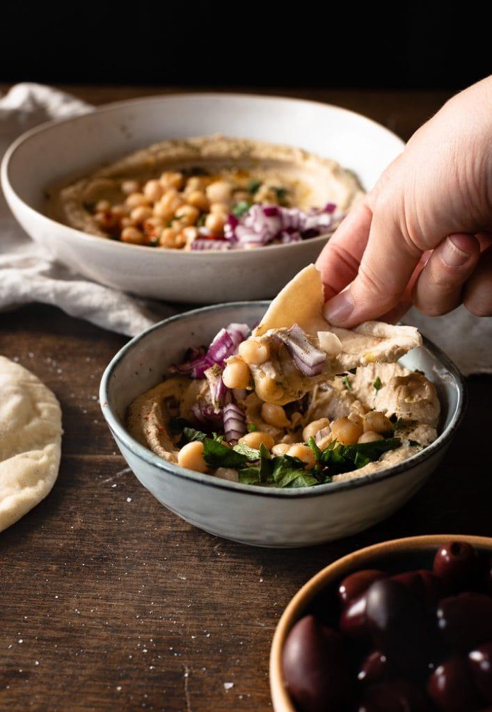 Hummus wird mit Pitabrot aufgetunkt.