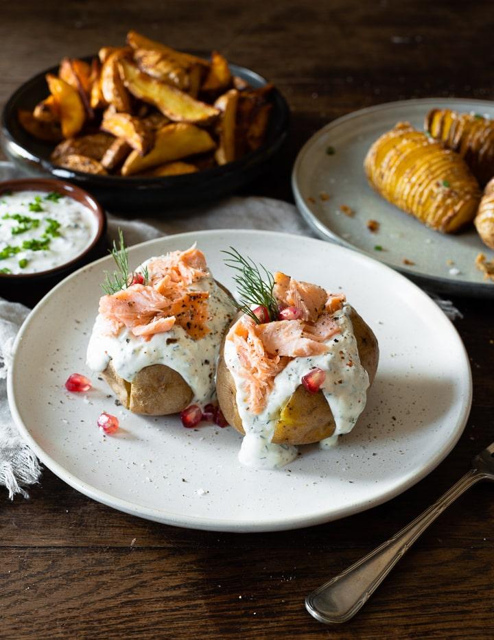 Ofenkartoffeln mit Kräuterquark, Stremellachs, Dill und einigen Granatapfelkernen. Im Hintergrund die sie Fächerkartotteln und die Kartoffelspalten zu sehen.