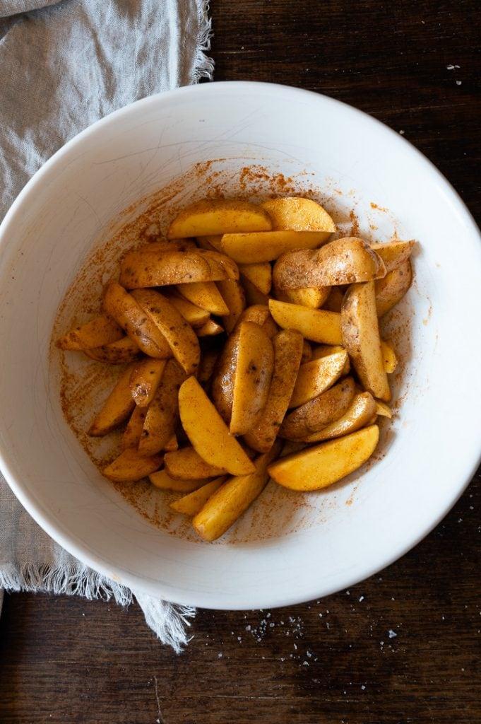 Kartoffelspalten vor dem Backen. Die Kartoffelspalten sind bereits mit Öl und Gewürzen mariniert.