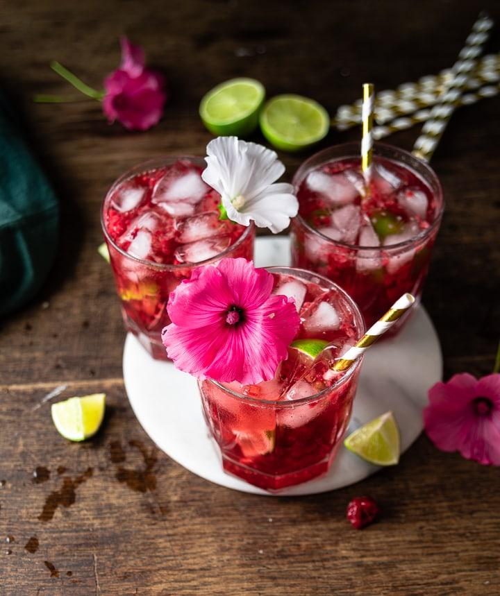 Drei Hibiskus Cocktails auf einem braunen Tisch.