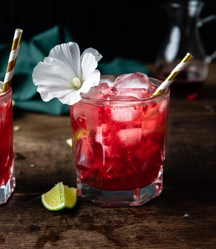 Der Hibiskus Cocktail mit vielen Eiswürfeln und einem goldenen Strohhalm.