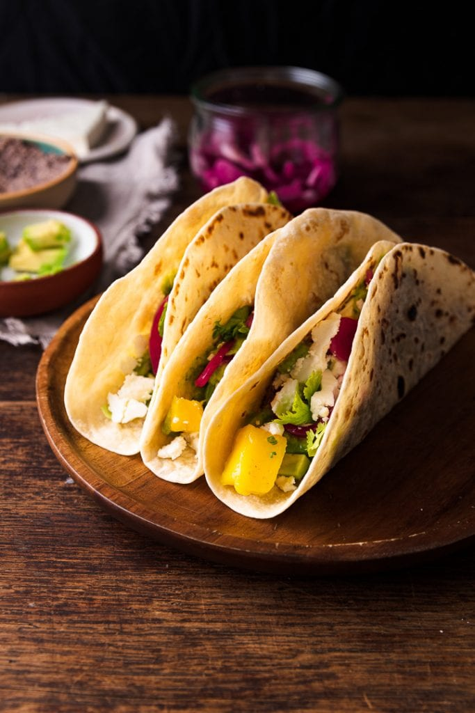 Drei leckere vegetarische Tacos auf einem Tisch.