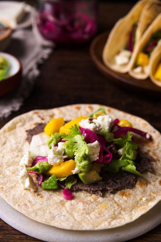 Ein Taco wird mit Mango, Zweibeln, Avocado, Bohnenpaste und Feta belegt. Er ist vegetarisch.