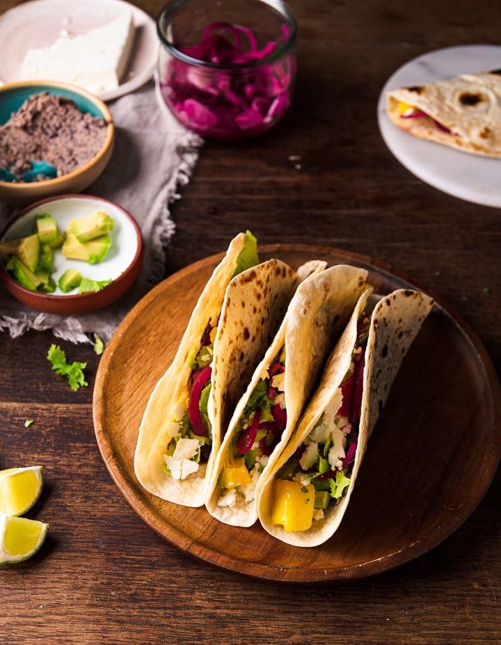Drei vegetarische Tacos auf einem Holzteller.