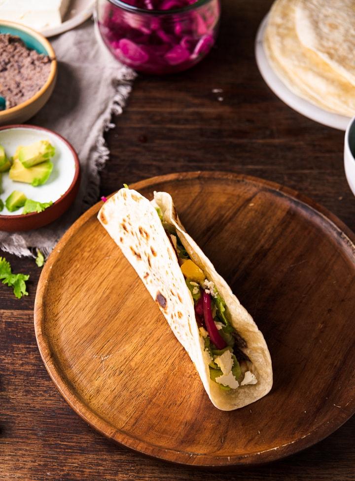 Ein vegetarischer Taco auf einem Holzteller.