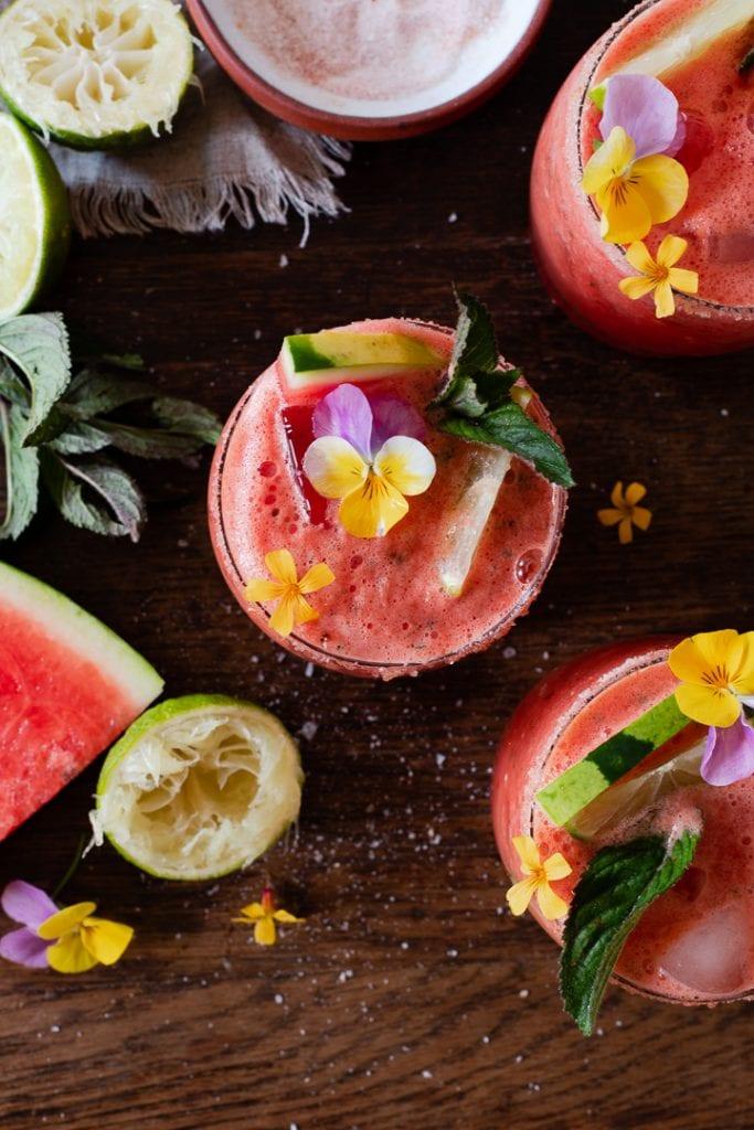 Wassermelonen Cocktail auf Eis mit Melonenspalten, Minze und essbaren Blüten serviert.