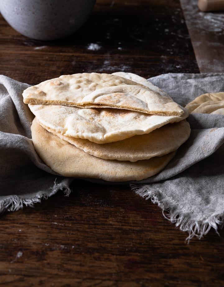 Pita Brot selber machen ist nicht schwer. Es liegen drei auf dem Tisch.