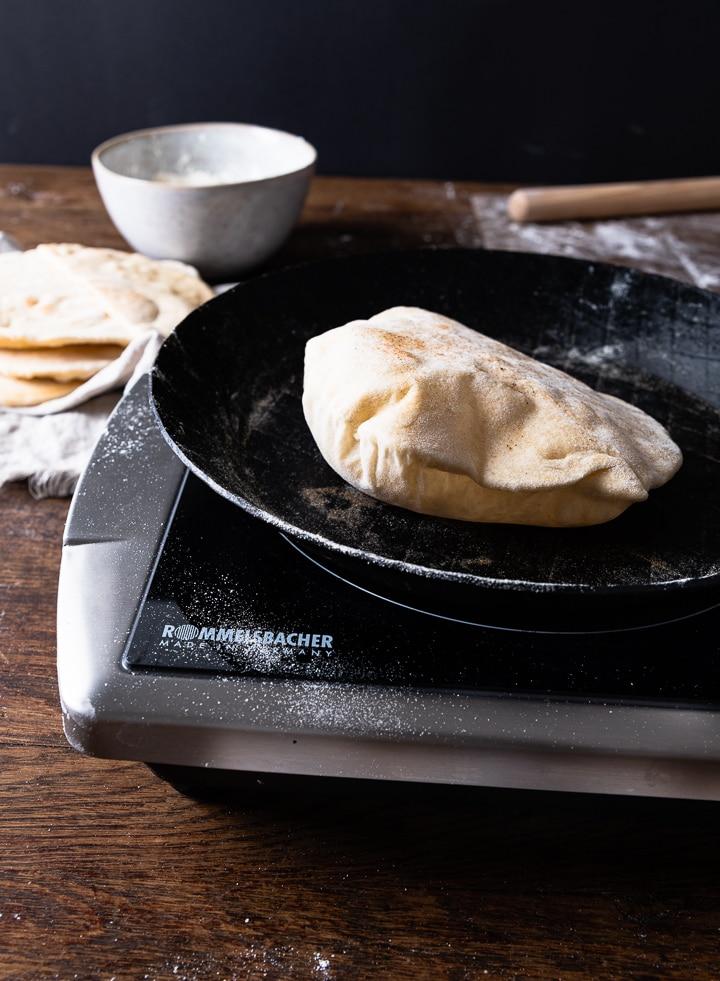 Das Pita Brot geht in der Pfanne auf.