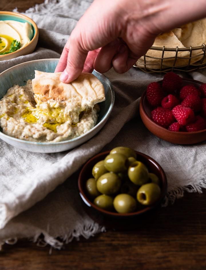 Ein selbstgemachtes Pita Brot wird in Hummus eingetaucht.