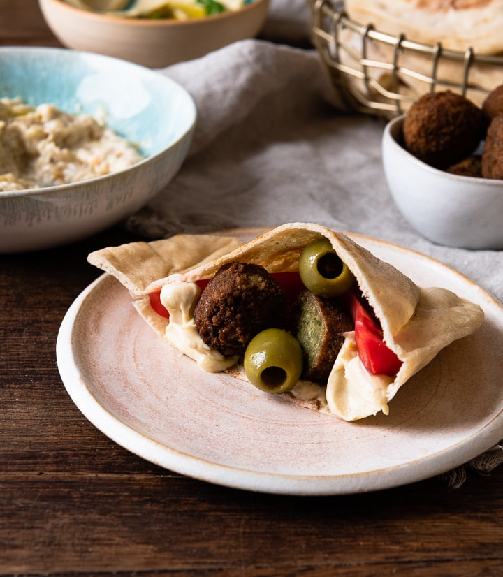 Ein gefülltes Pita Brot mit Falafel, Oliven und Hummus.