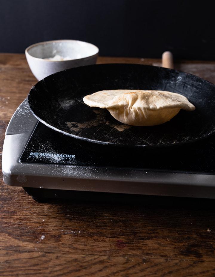 Wir machen ein Pita Brot selber in einer Pfanne.