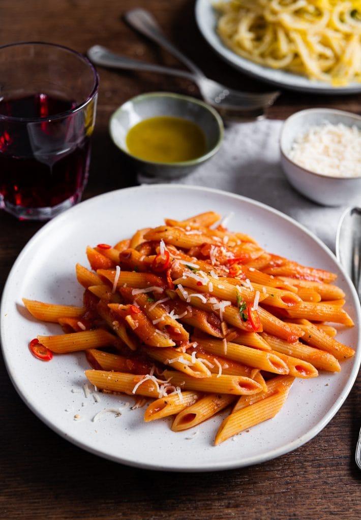 Parmesan wird über die Penne Arrabiata gestreut