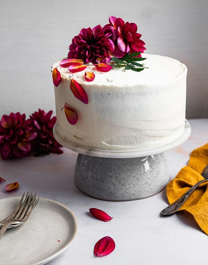 Eine weiße Geburtstagstorte auf einem Teller mit frischen Blumen.