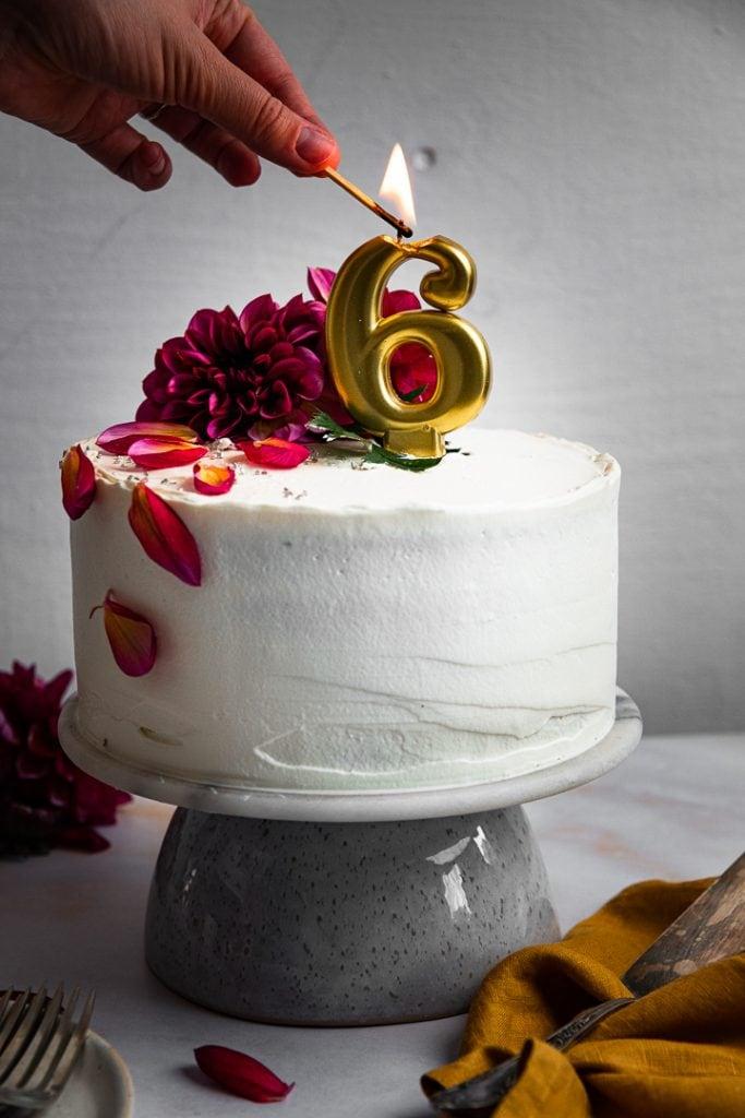Eine Kerze wird auf der Geburtstagstorte angezündet.
