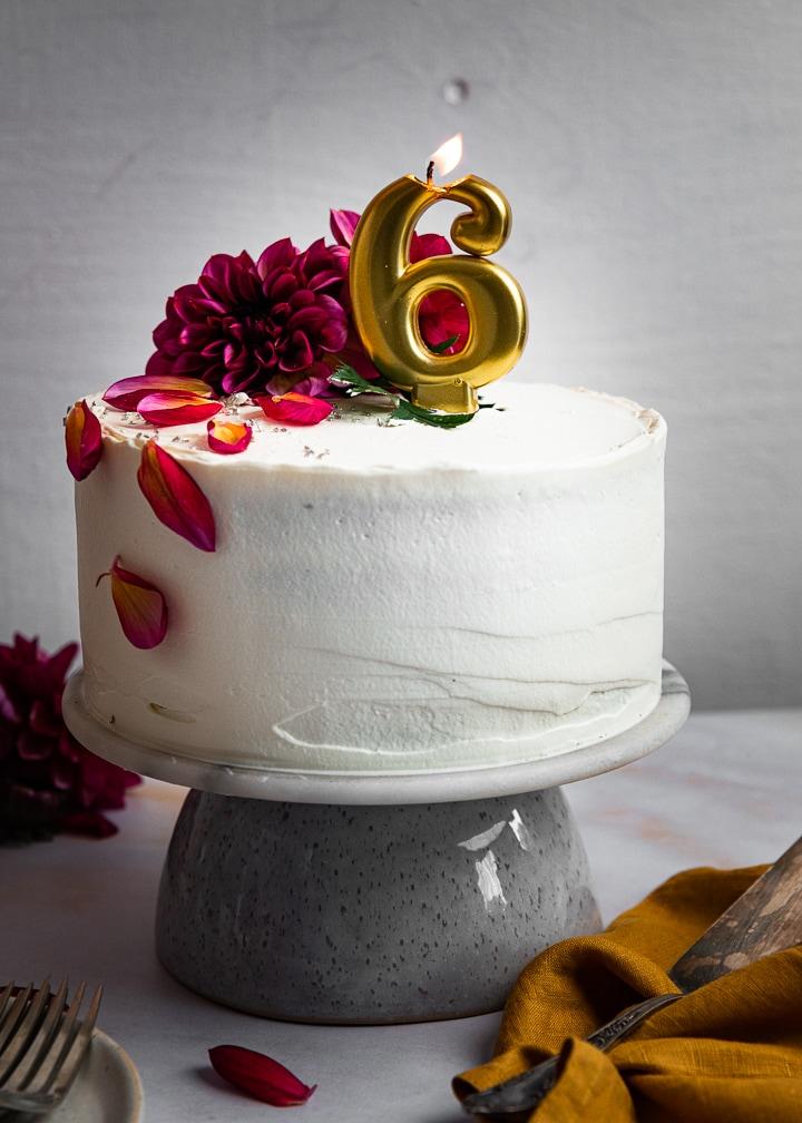 Selbstgemachte Geburtstagstorte mit einer angezündeten 6 als Kerze.